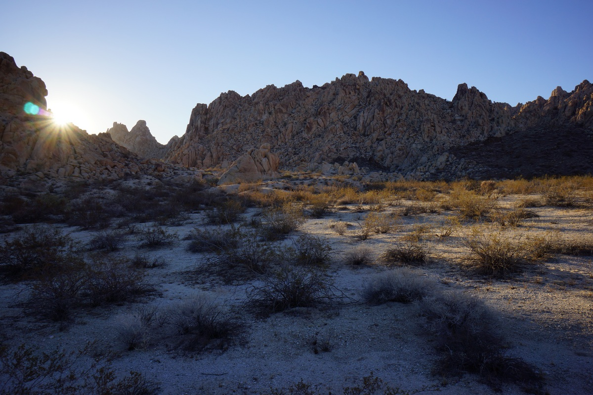 sun peaking over mountain in the desert