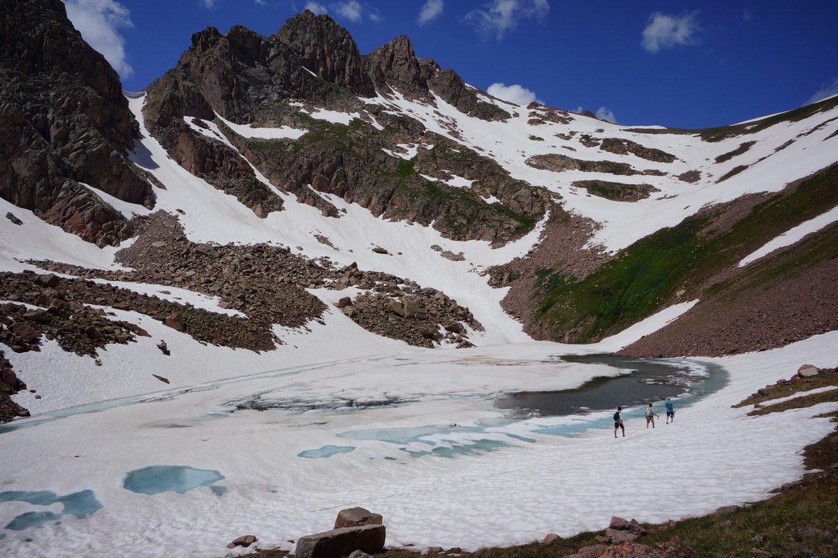 3 hikers walking around snow lake in july - gore mountains, colorado