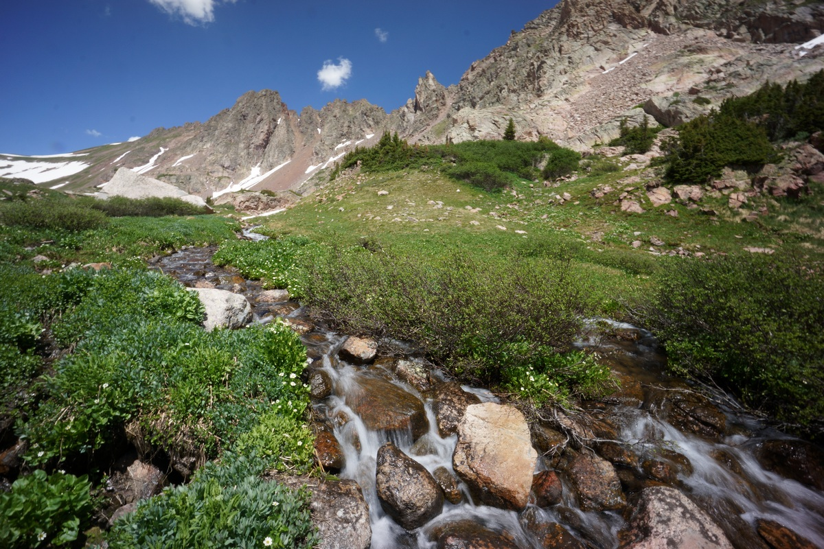 small mountain stream runs through green meadow in july - colorado's gore mountains