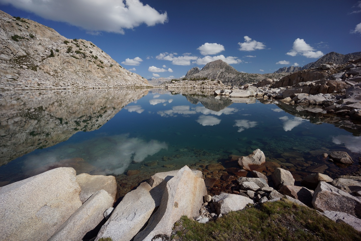 unnamed lake in upper mcgee canyon with clouds reflecting in blue water