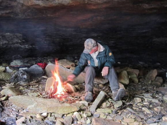 taking shelter in a cave, warming up with a fire