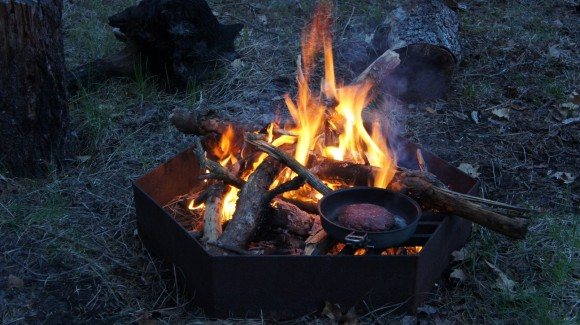 cooking a hamburger over a fire in a pan while backpacking