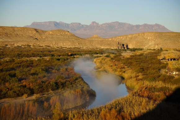 mist over the rio grande river during sunrise with the chisos mountains in the background