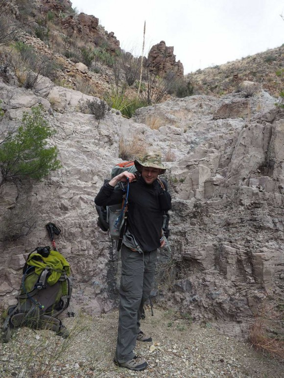putting the backpack on again after climbing down a pour off in a canyon in big bend