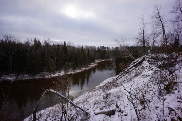 hiking along the manistee river with snow on ground