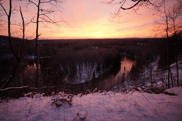 pink sky sunrise in winter over manistee river in michigan